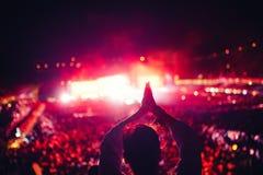 Schattenbild einer Frau, die Festivallichter und -konzert genießt Frau, die Handzeichen am Konzert macht Lizenzfreie Stockfotografie
