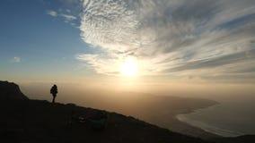 Schattenbild einer Frau, die Fotos eines unglaublichen Sonnenuntergangs auf die Oberseite eines Berges über dem Ozean auf Kanari stock footage