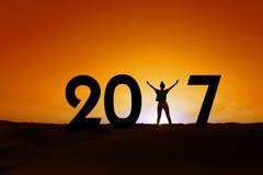 2017, Schattenbild einer Frau, die im Sonnenuntergang, Konzept des neuen Jahres steht Stockbild