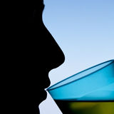 Schattenbild einer Frau, die von einem Glas trinkt Lizenzfreies Stockfoto