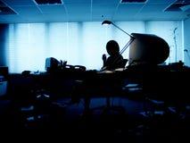 Schattenbild einer Frau in einem dunklen Büro Stockfotografie