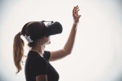 Schattenbild einer Frau in einem Sturzhelm der virtueller Realität Stockbild