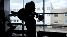 Schattenbild einer Frau am Fenster anhebenden Barbell für Schultermuskeln stock video