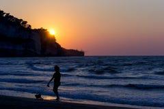 Schattenbild einer Frau mit Hund auf Küstenvorland während des Sonnenuntergangs für Ferien und Sommerferienkonzept Stockfotografie