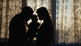 Schattenbild einer glücklichen Familie Sind das Haus am Fenster bei Sonnenuntergang, halten leicht das Kind in Ihren Armen stock footage