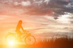 Schattenbild einer glücklichen Frau außerhalb des Fahrens Weinlesefahrrads Lizenzfreies Stockfoto