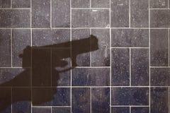 Schattenbild einer Hand, die ein Gewehr hält Lizenzfreie Stockbilder