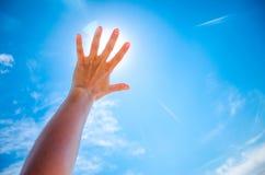 Schattenbild einer Hand gegen einen Sonnenuntergang Stockfotografie