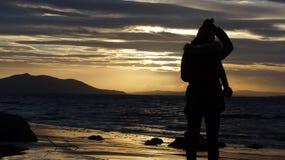 Schattenbild einer jungen Dame gegen das Meer während des Sonnenuntergangs Stockbild