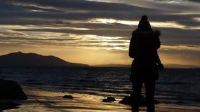 Schattenbild einer jungen Dame gegen das Meer während des Sonnenuntergangs Stockfotografie