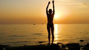 Schattenbild einer jungen Frau auf dem Seestrand, der in einem Badeanzug steht und seine Hände oben anhebt stock footage