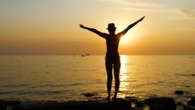 Schattenbild einer jungen Frau auf dem Strand w?hrend des Sonnenuntergangs, der in einem Badeanzug steht und seine H?nde oben anh stock video footage
