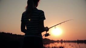 Schattenbild einer jungen Frau, die auf Naturfischen auf einer Angelrute durch das Spinnen an der Dämmerung stillsteht stock footage
