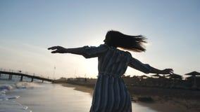 Schattenbild einer jungen Frau, die herum mit ihren Armen offen, Mädchen im Sonnenlicht spinnt mit Aufregung auf Strand spinnt stock video footage