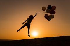 Schattenbild einer jungen Frau, die mit Ballonen bei Sonnenuntergang spielt Lizenzfreie Stockbilder