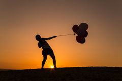 Schattenbild einer jungen Frau, die mit Ballonen bei Sonnenuntergang spielt Stockfoto