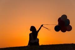 Schattenbild einer jungen Frau, die mit Ballonen bei Sonnenuntergang spielt Lizenzfreies Stockbild