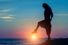 Schattenbild einer jungen Frau setzt seinen Fuß auf die Seesonnenuntergangsonne Stockfotos