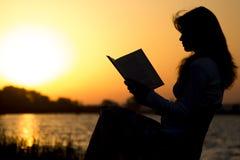 Schattenbild einer jungen Schönheit an der Dämmerung, die auf einem Klappstuhl sitzt und sorgfältig entlang des offenen Buches an Stockbild