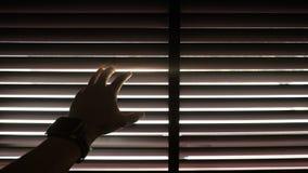 Schattenbild einer männlichen Hand, welche die Digitaluhr öffnet den hölzernen blinden Vorhang mit Morgensonnenlichteffekt trägt lizenzfreie stockfotografie