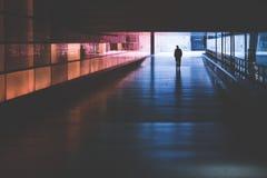 Schattenbild einer Person, die in einen dunklen Tunnel geht Stockbild