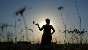 Schattenbild einer schlanken Frau, die eine Kamera auf einem Gebiet bei Sonnenuntergang in SlomO wirft stock video