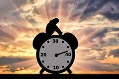 Schattenbild einer traurigen Frau, die auf einer Uhr sitzt, in der der Pfeil fast 40 Jahre alt zeigt stockfotografie