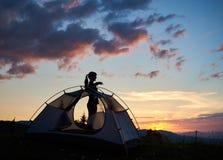 Schattenbild eines attraktiven Mädchens, das im Profil nahe dem Zelt unter dem Morgenhimmel am Tagesanbruch steht Lizenzfreie Stockfotos