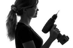 Schattenbild eines Bauarbeiters der jungen Frau mit einem Schraubenzieher und Schutzbrillen Lizenzfreies Stockfoto