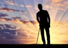 Schattenbild eines behinderten Mannes stützt sich mit einer Krücke Stockbild