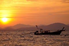 Schattenbild eines Bootes, das während des Sonnenuntergangs schwimmt Lizenzfreie Stockbilder