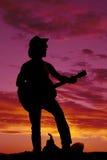 Schattenbild eines Cowboyfußes auf dem Sattel, der Gitarre spielt Lizenzfreie Stockfotografie
