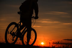 Schattenbild eines Fahrrades auf Himmelhintergrund während des Sonnenuntergangs Lizenzfreie Stockfotos