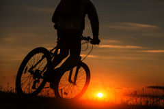 Schattenbild eines Fahrrades auf Himmelhintergrund während des Sonnenuntergangs Lizenzfreies Stockbild