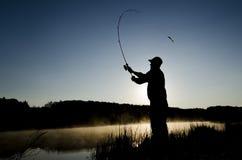Schattenbild eines Fischers bei Sonnenaufgang mit einer Stange lizenzfreie stockfotos