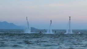 Schattenbild eines Fliegenbrettreiters, drei Leute, Show, Weltcup, synchrone Leistung stock footage