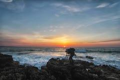 Schattenbild eines Fotografen mit einem Rucksack und einem Stativ Stockfoto