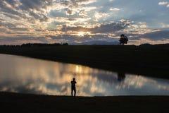 Schattenbild eines Fotografen zur Sonnenuntergangzeit Stockbild