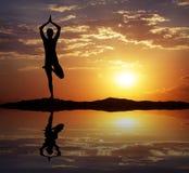 Schattenbild eines Frau Yoga am Abend Stockfotografie