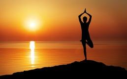 Schattenbild eines Frau Yoga am Abend Lizenzfreie Stockfotografie