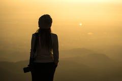Schattenbild eines Frauenphotographen, der in der trockenen Rasenfläche steht Stockfotografie