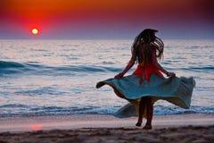 Schattenbild eines Frauentanzens durch den Ozean an den Sonnen Stockbild