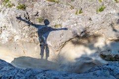 Schattenbild eines glücklichen Menschen im Freien auf den Felsen, mit seinen Armen Lizenzfreie Stockbilder