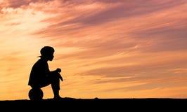Schattenbild eines Jungen, der auf Fußball oder Fußball sitzt Lizenzfreie Stockfotos