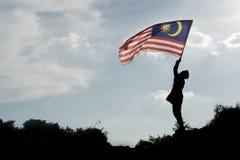 Schattenbild eines Jungen, der die malaysische Flagge feiert den Malaysia-Unabhängigkeitstag hält lizenzfreies stockbild