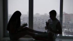 Schattenbild eines jungen glücklichen Paars, das auf dem Fenster vor Tag des verschneiten Winters sitzt stock footage