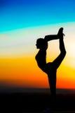 Schattenbild eines jungen Mädchens auf dem Sonnenunterganghintergrund Stockfoto