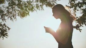 Schattenbild eines jungen Mädchens, das eine Mitteilung am Telefon in den Strahlen der Glättungssonne schreibt stock video