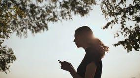 Schattenbild eines jungen Mädchens, das eine Mitteilung am Telefon wählt stock footage