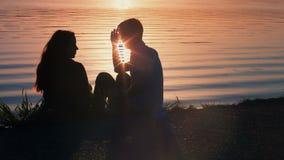 Schattenbild eines jungen Paares, das am Strand küßt stock video footage